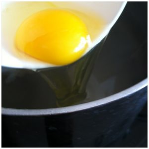 3. Crack one egg into a small bowl and tranfer it to the hot water bath. Don't stir it. Repeat with the other egg.